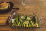 High angle view of asparagus and lemon in tray by chicken meat on table - CAVF22592