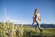 Low angle view of female hiker walking on field against sky - CAVF22604