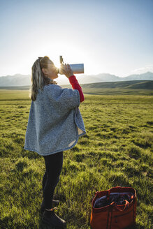 Side view of female hiker drinking water while standing on grassy field against clear sky - CAVF22607