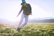Female hiker jumping on grassy field against sky - CAVF22610