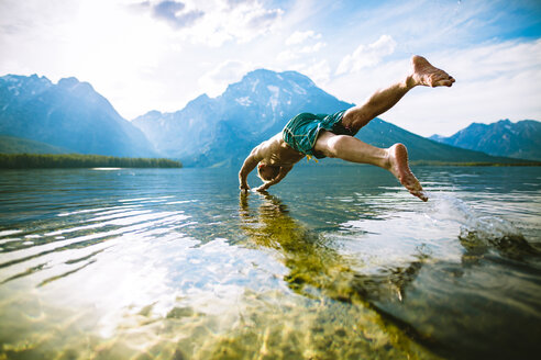 Man diving into lake against mountains and sky - CAVF22616