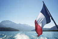 French flag over Lake Annecy against clear sky - CAVF22643