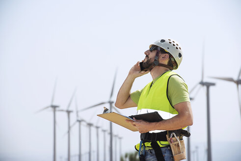 Engineer using smart phone at wind farm - CAVF22700