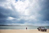 Rear view of senior man standing by off-road vehicle at Inskip Point against cloudy sky - CAVF22778