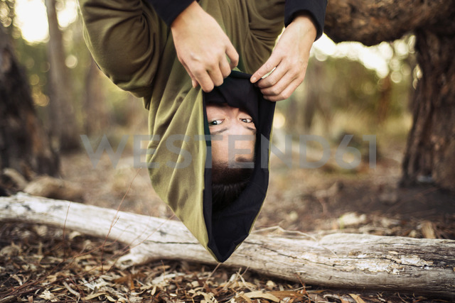 Portrait of woman in hooded jacket hanging upside down from tree - CAVF22823
