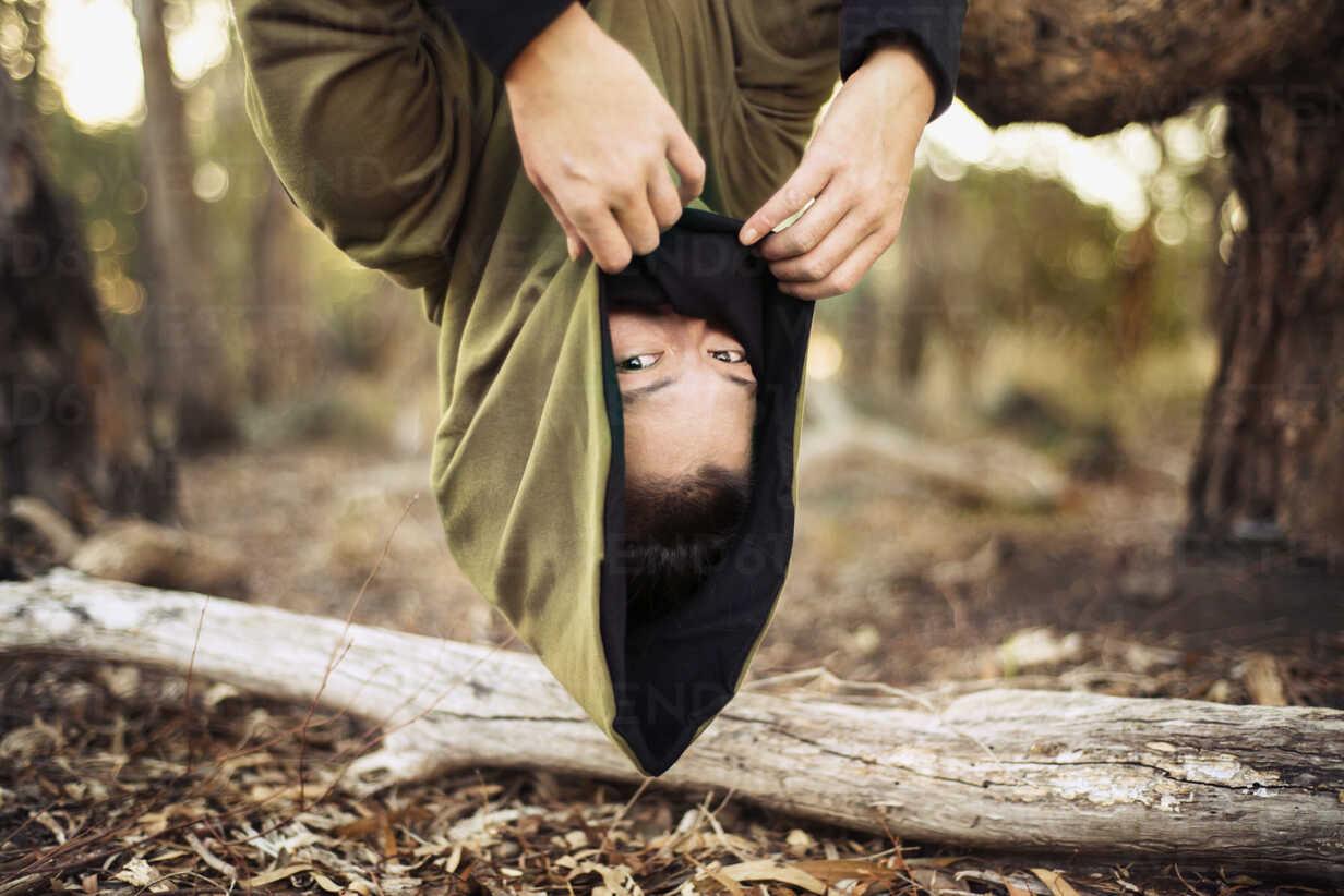 Portrait of woman in hooded jacket hanging upside down from tree - CAVF22823 - Cavan Images/Westend61
