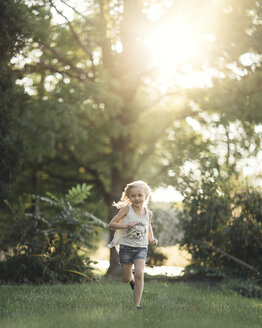 Happy girl running on grassy field against trees during sunny day - CAVF22940