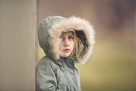 Portrait of thoughtful girl wearing fur hood standing against wall - CAVF22943