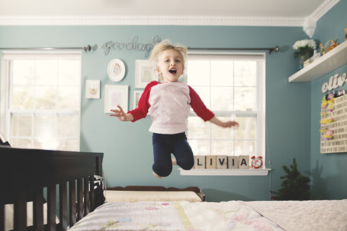 Cute girl jumping on bed against wall at home - CAVF22946