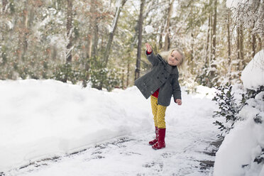 Cheerful girl playing on snow covered field at park - CAVF22952