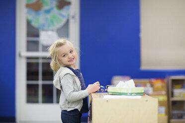 Portrait of cute smiling girl standing by table at school - CAVF22958