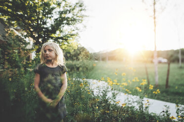 Thoughtful girl standing amidst plants in yard - CAVF22961