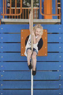 Cute girl playing on pole against wooden structure at playground - CAVF22967