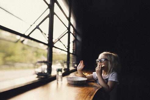 Girl wearing eyeglasses having food while sitting at table by window in darkroom - CAVF22973