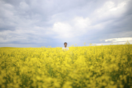 Mid distance of man on oilseed rape field against cloudy sky - CAVF23033