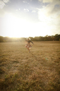 Happy girl playing on grassy field against sky - CAVF23096