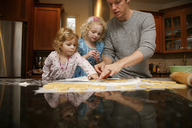 Father with daughters making cookies at table in kitchen - CAVF23111