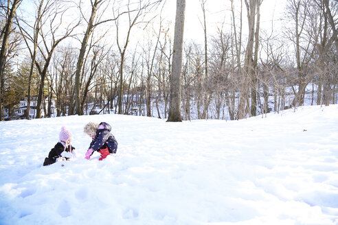 Sisters playing on snow covered field - CAVF23114