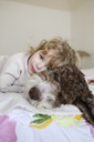 Portrait of happy girl relaxing with dog on bed at home - CAVF23120