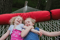 High angle view of happy sisters lying on hammock at yard - CAVF23156