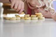 Midsection of girl playing with macaroon on table at home - CAVF23168