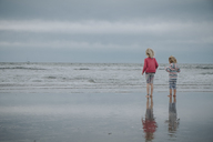 Rear view of sisters standing at beach against sky - CAVF23177