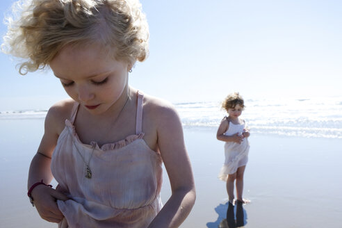 Sisters standing at beach against sky - CAVF23180