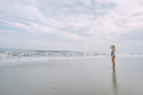 Full length of girl standing at Cape May Beach against cloudy sky - CAVF23201