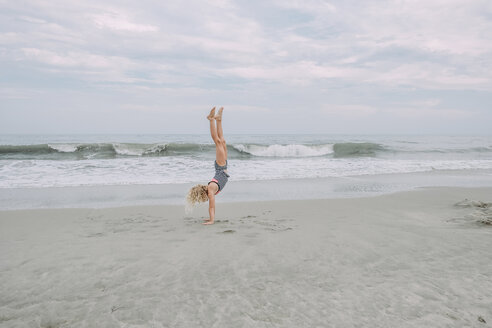 Full length of girl doing handstand at Cape May Beach against sea and sky - CAVF23204