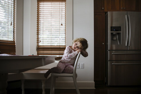 Sad girl sitting on chair at home - CAVF23210