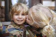 Portrait of happy girl while sister kissing her - CAVF23216