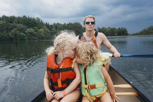 Sister kissing girl while father canoeing in lake against stormy clouds - CAVF23222