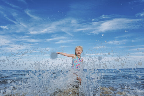 Portrait of playful girl splashing water while standing in sea against cloudy sky - CAVF23237