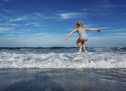 Full length of playful girl with arms outstretched jumping over shore against sky - CAVF23240
