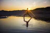 Woman wearing bikini doing yoga at beach during sunset - CAVF23279