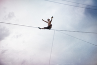 Low angle view of man balancing on rope while slacklining against cloudy sky - CAVF23318