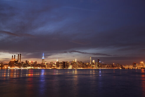 Scenic view of river and illuminated cityscape against cloudy sky at night - CAVF23372