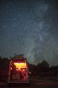 Man sitting in illuminated camper van against star field at night - CAVF23447