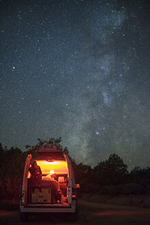Man sitting in illuminated camper van against star field at night - CAVF23447