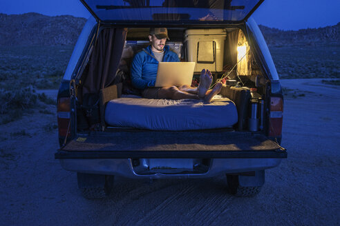 Hiker using laptop in car trunk during vacation - CAVF23480
