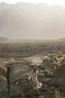 Young woman walking on rocks in field against mountains - CAVF23483