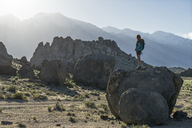 Full length of female hiker looking at Alabama Hills while standing on rock - CAVF23486