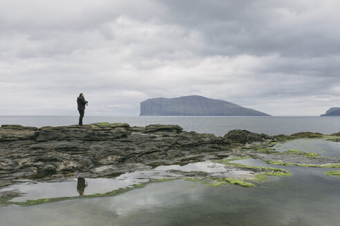 Hiker standing on rocks against sea and cloudy sky - CAVF23564