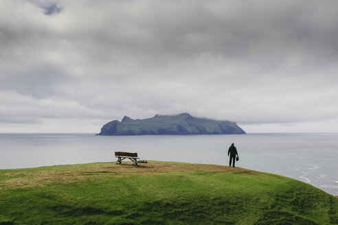 Hiker looking at view while standing on hill by sea against stormy clouds - CAVF23600