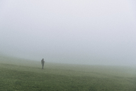 Hiker standing on field during foggy weather - CAVF23609
