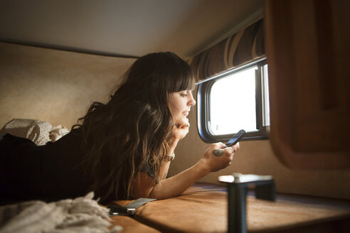 Woman relaxing on bed by window while using smart phone in camper van - CAVF23681