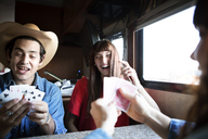 Happy friends playing cards at table while travelling in camper van - CAVF23687