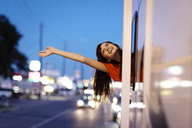 Cheerful woman waving while leaning out of camper van - CAVF23708