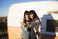 Female friends taking selfie while standing by camper van - CAVF23711