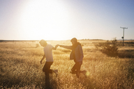 Couple walking while holding hands on field against clear sky - CAVF23717